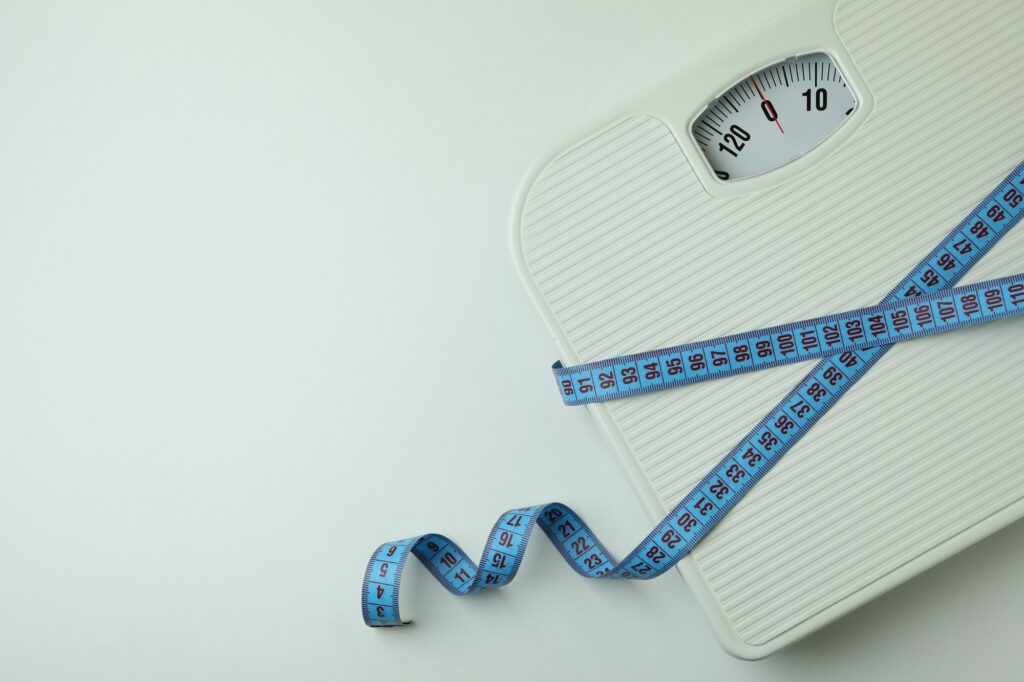 Scales with measuring tape on white background